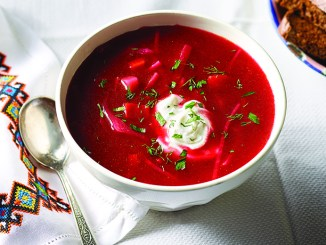 Bowl of borscht on white background