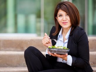 Businesswoman sitting outside on steps eating a salad for lunch