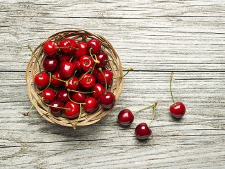 Fresh red cherries in basket on wooden table
