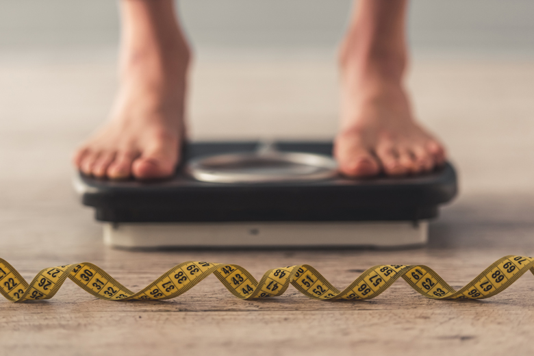 Cropped image of woman feet standing on weigh scale