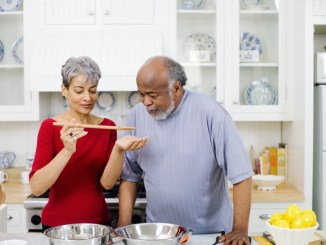 Older couple cooking and tasting dishes together in a kitchen
