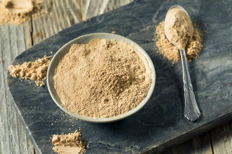 Maca powder in a bowl and a spoon