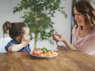Mother introducing brocolli to child