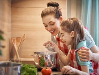 Healthy food at home. Happy family in the kitchen. Mother and child daughter are preparing on the cooker.