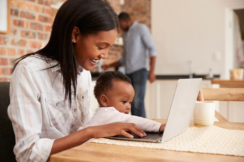 African American woman interacting with baby while studying at computer
