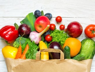 Full paper bag of different fruits and vegetables on a white wooden background.