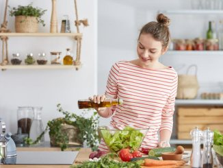Woman in kitchen pouring oil onto salad greens