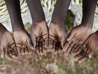 African children gather hands together