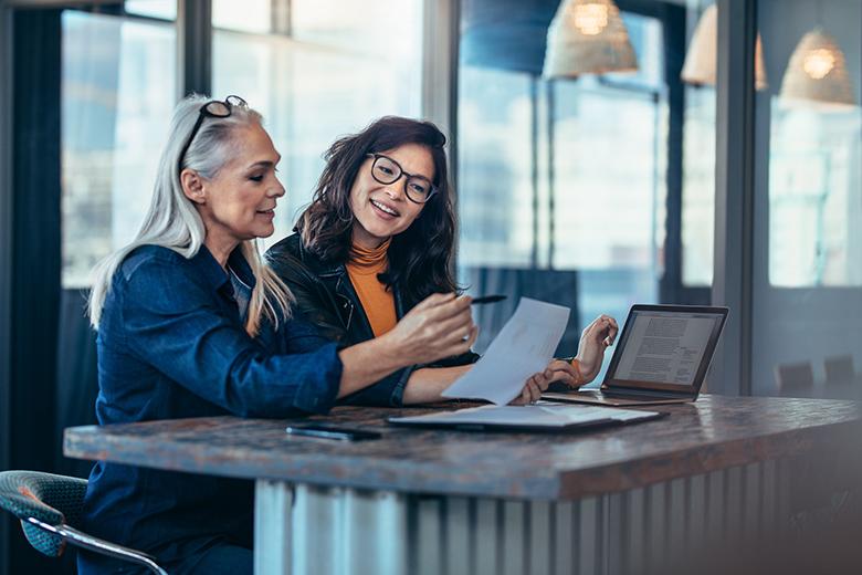 two women talking looking at laptop
