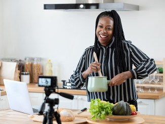 Happy woman vlogger broadcasting live video online while cooking food in kitchen at home