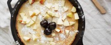 Dutch baby with fresh fruits and icing sugar in skillet