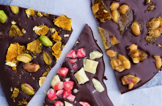 three large pieces of chocolate triangles sprinkled with orange green pistachios pink and white candy white chocolate and peanut toffee
