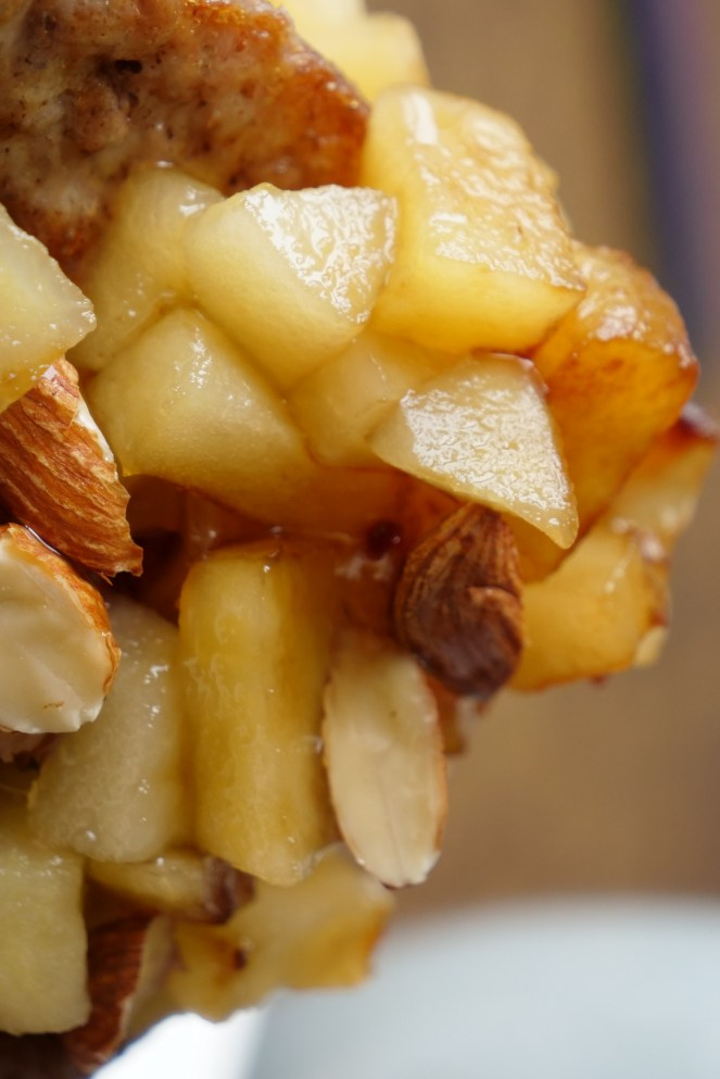 stack of caramel apples with almonds and syrup drizzled on top