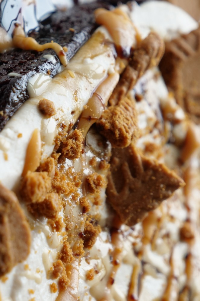 brownie topped with cream, biscoss spread, cookies and caramel dripping down sides on white surface