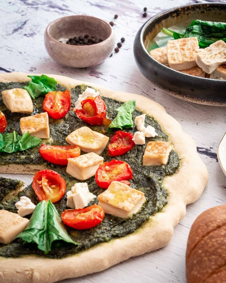 pizza topped with tomatoes, tofu, spinach and pesto on white rustic wooden boards lying next to garlic bread, loose peppercorns and toppings