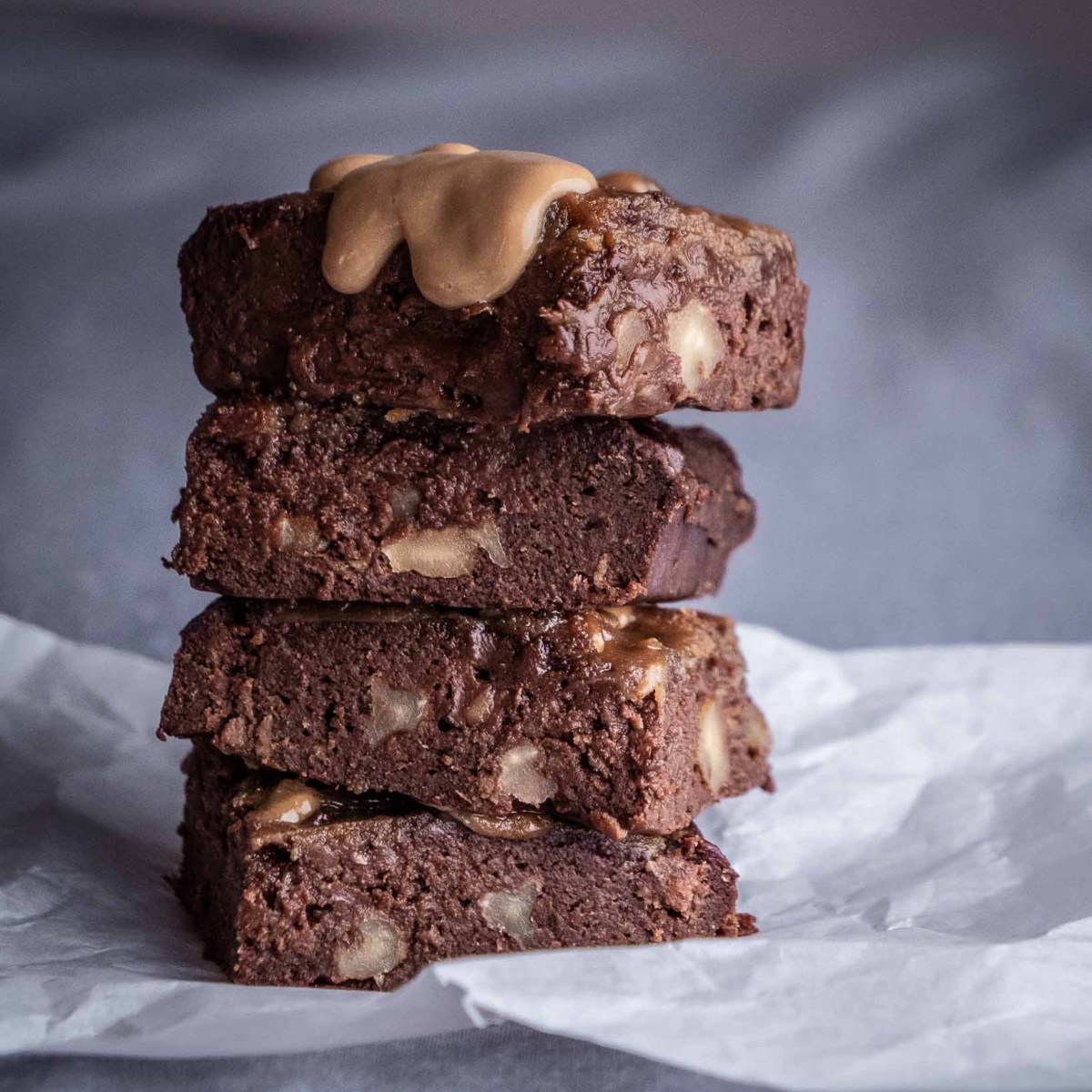 stack of gooey fudgy chocolate vegan brownies studded with walnuts and drizzled with peanut butter dripping down edges
