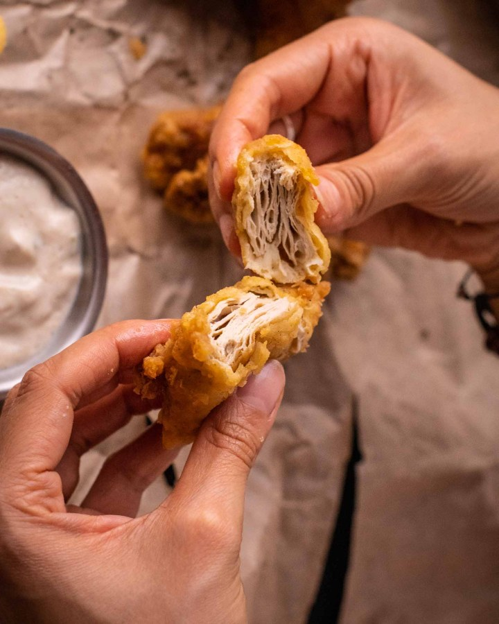 piece of fried chicken being pulled apart between both hands to reveal inner succulent faux chicken