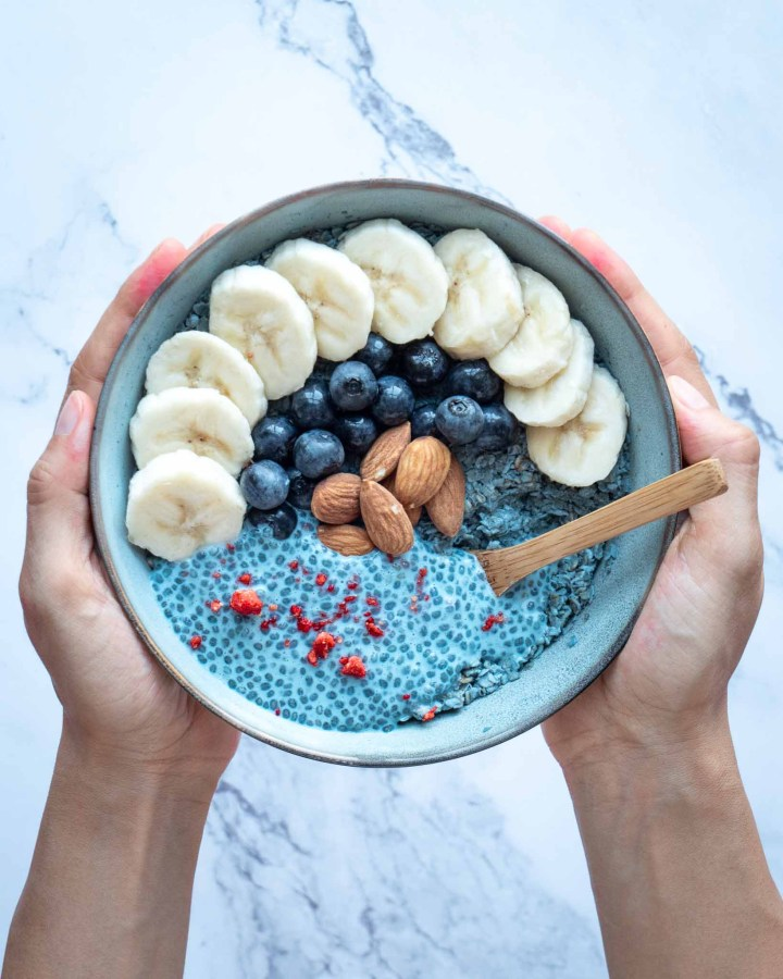 hands holding bowl of blue overnight oats sprinkled with blue chia pudding, bananas, almonds, blueberries and strawberry chips