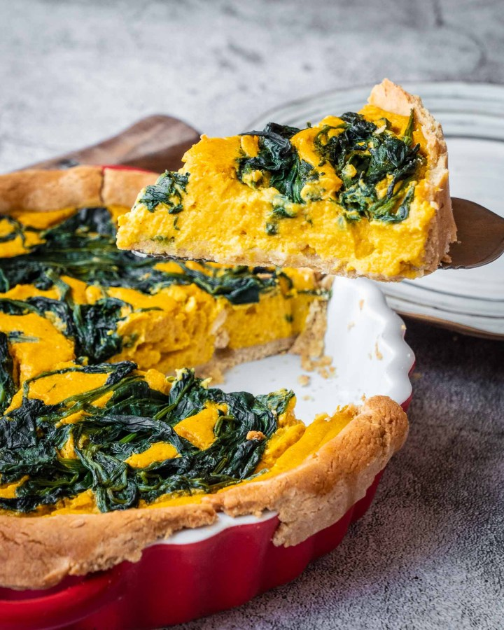 slice of bright yellow and green vegan spinach pumpkin tart being taken from whole pie in red ceramic pie dish