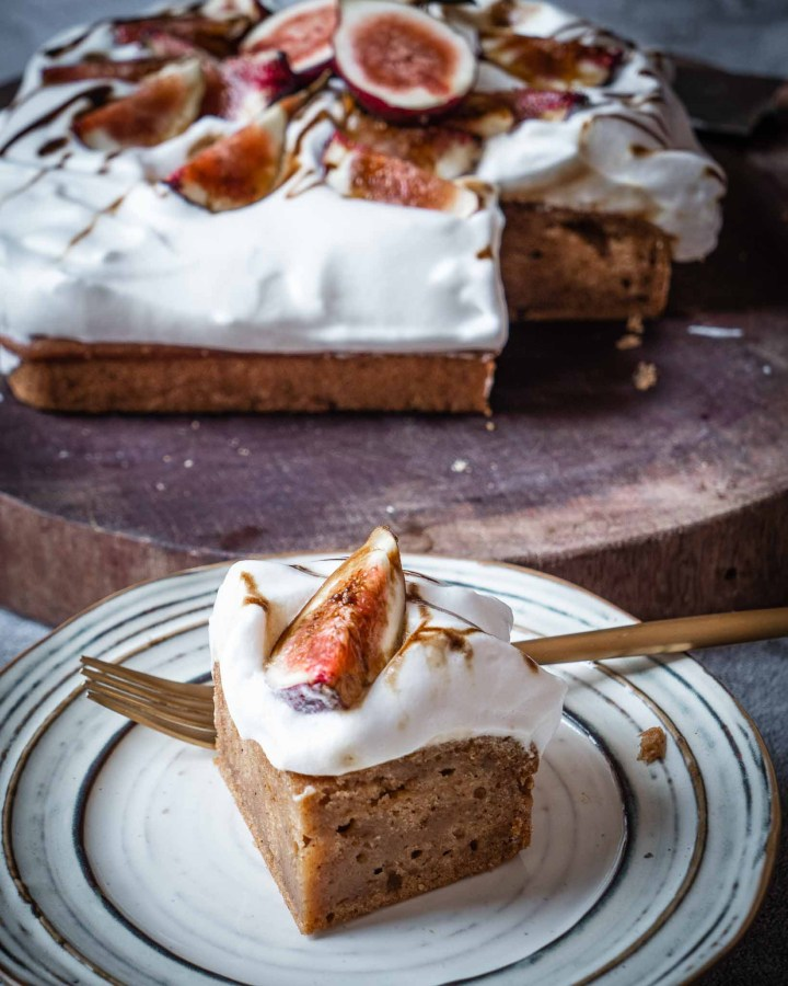 corner slice of golden olive oil sponge cake topped with white fluffy frosting and figs on white pottery plate with large cake behind