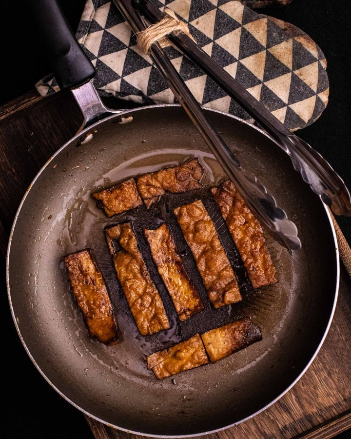 dark lit vegan bacon frying in a frying pan with metal tongs and black and white oven glove next to it