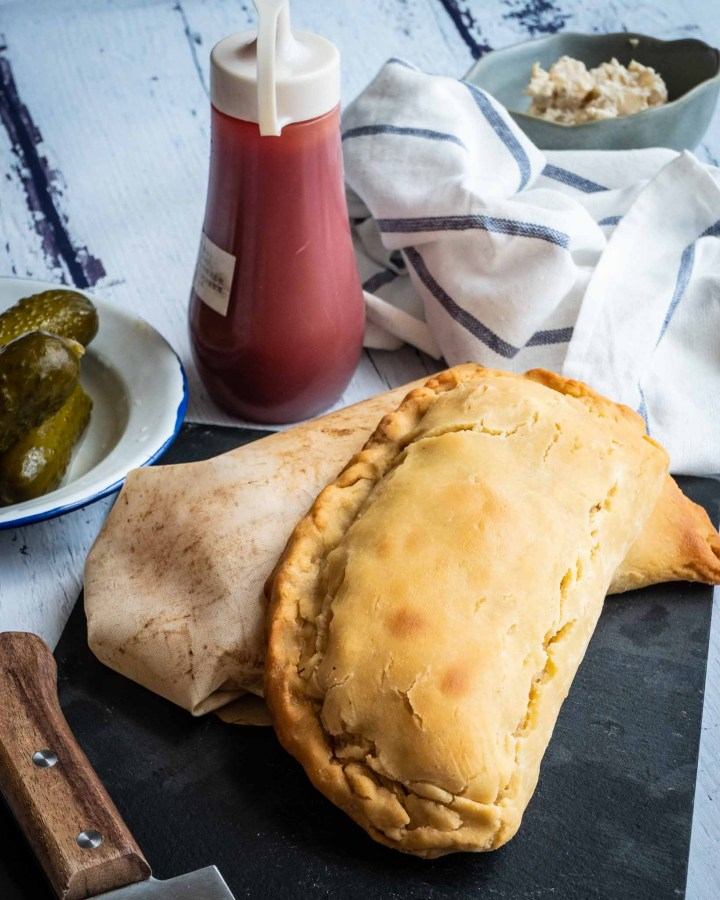 two golden cornish pasties laying next to each other on white wooden table next to ketchup  bottle and gherkins