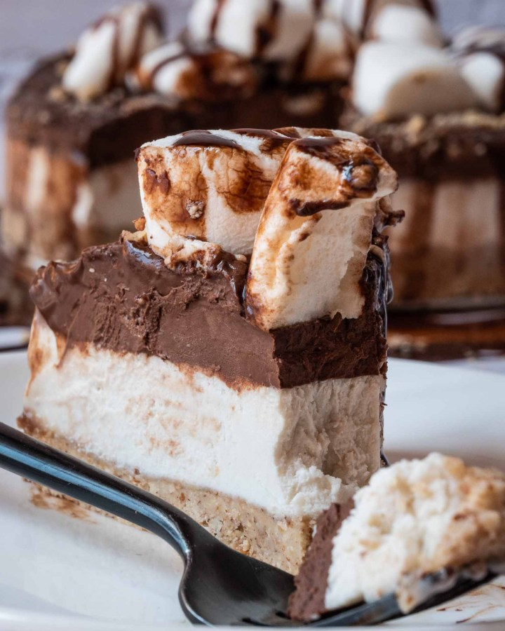 slice of vegan no bake cheesecake with bottom biscuit layer, cream centre and chocolate top layer with marshmallows and chocolate sauce