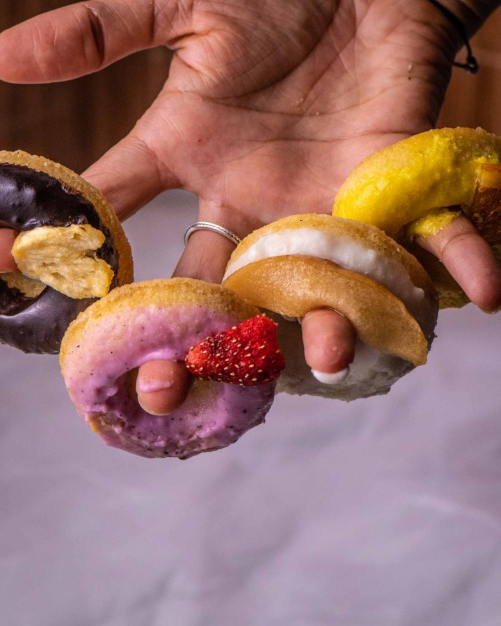 4 mini doughnuts on 4 fingers on hand, 1 with chocolate frosting, 1 pink frosting, 1 yellow frosting and 1 white frosting