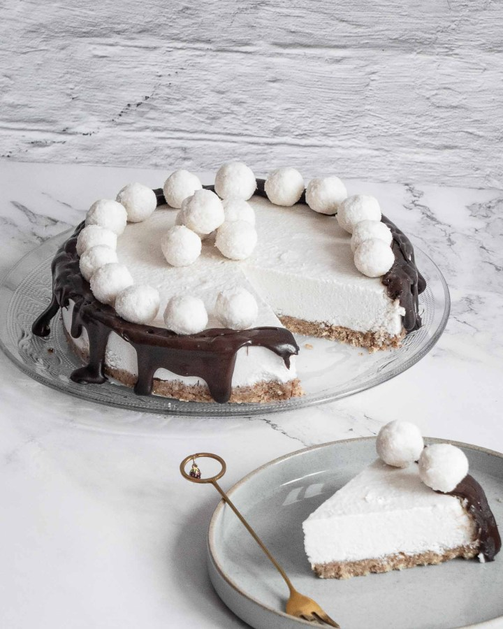 white cheesecake with white snowballs on top and dark chocolate dripping down edges on white stone table in front of white brick wall