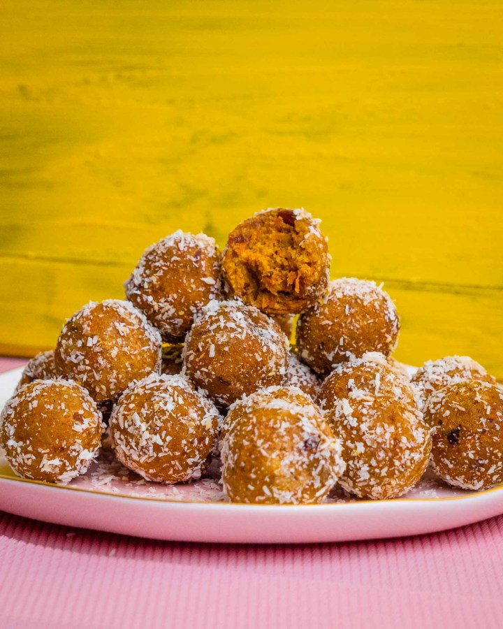 pink table with yellow wall with white plate filled with big pile of orange protein balls dusted with coconut shreds with bite taken to reveal moist chewy cake inside