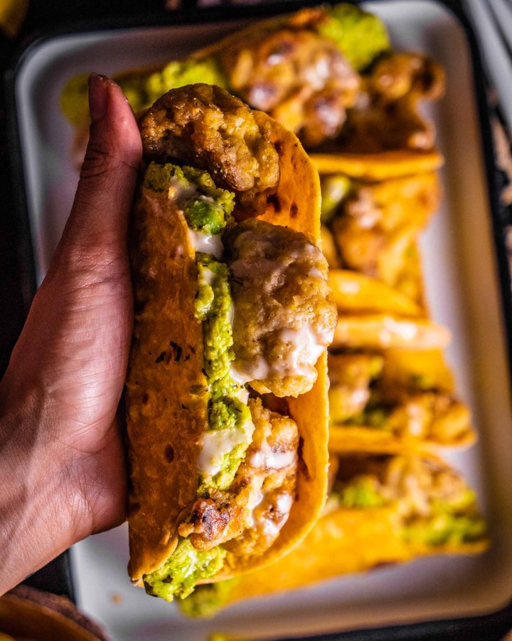 hand holding crispy corn taco filled with crispy cajun cauliflower and avocado drizzled with mayonnaise above tray filled with more tacos