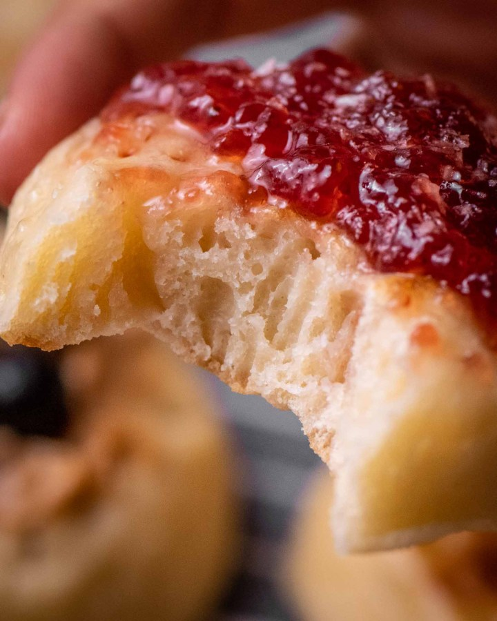 close up of crumpet with bite taken from it to reveal bubbly airy inside covered with butter and jam