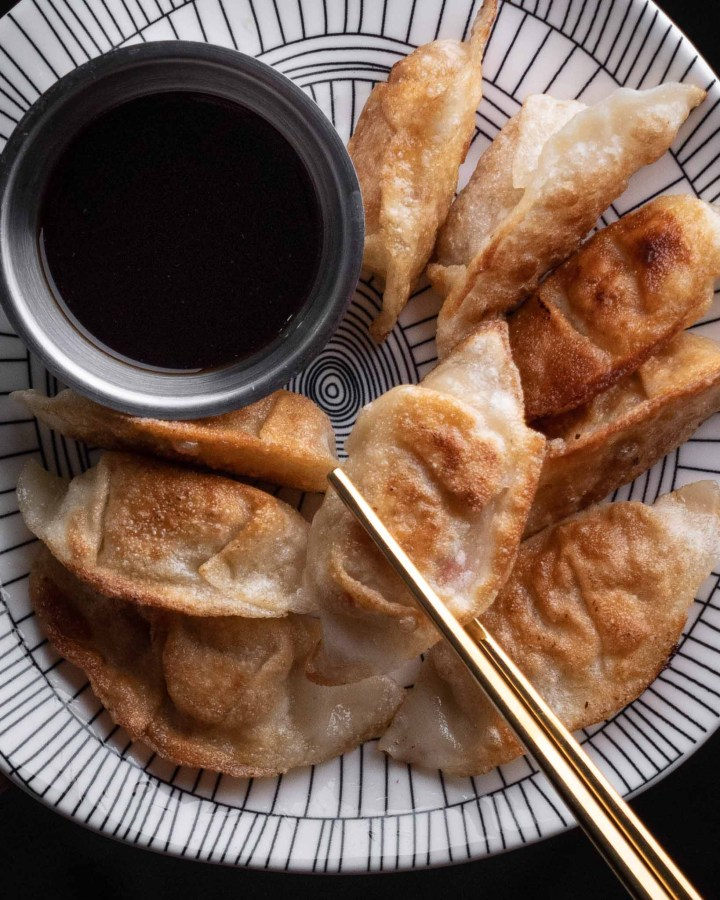 fried jiaozi on black and white plate next to small silver pot of soy sauce with gold chopsticks holding a dumpling