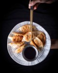 plate of fried crispy chinese dumplings next to gold chopsticks with pot of black vinegar