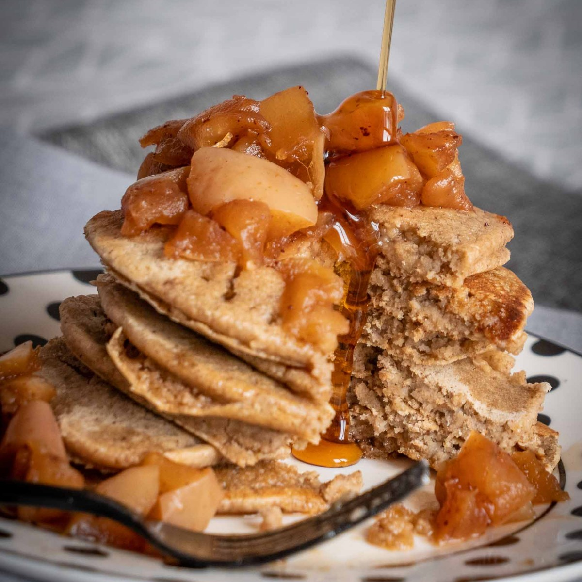 fluffy american style oat pancakes in large stack topped with caramel apples and being drizzled with syrup
