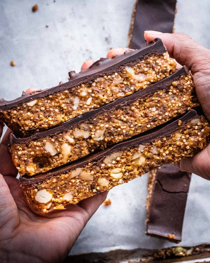 hand holding stack of peanut butter protein bars topped with chocolate layer and filled with nuts above white greaseproof paper