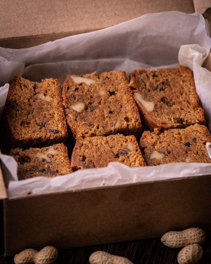 batch of homemade moist blondie cake squares in wooden box lined with white parchment paper