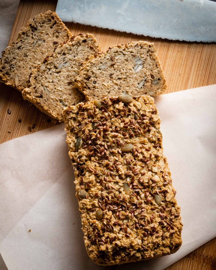loaf of homemade seeded bread cut into slices laying on rustic wooden board next to bread knife