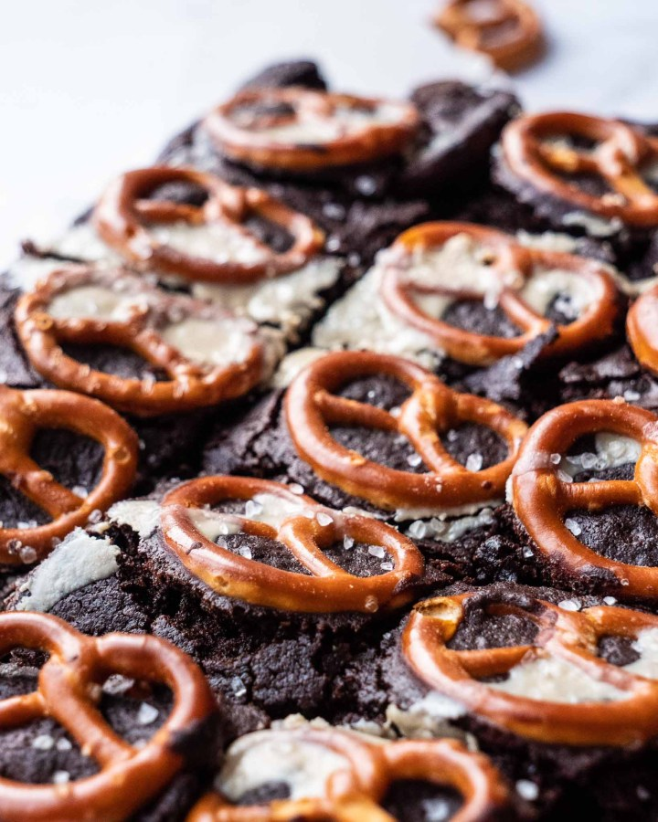 several vegan brownie chunks with neat rows of pretzels on surface drizzled with tahini and salt crystals