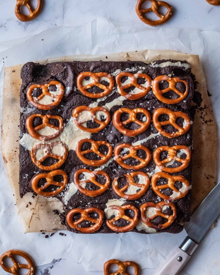 large brownie square with pretzels on top on white marble table with pretzels sprinkled around