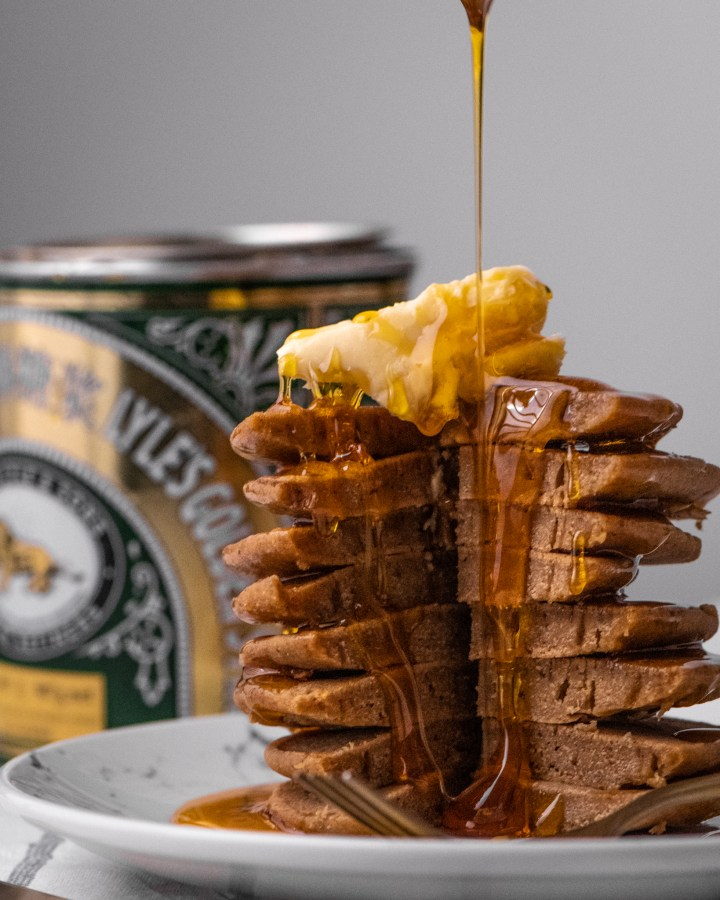 vintage style tin of lyles golden syrup being drizzled over tall stack of vegan pancakes topped with knob of vegan butter