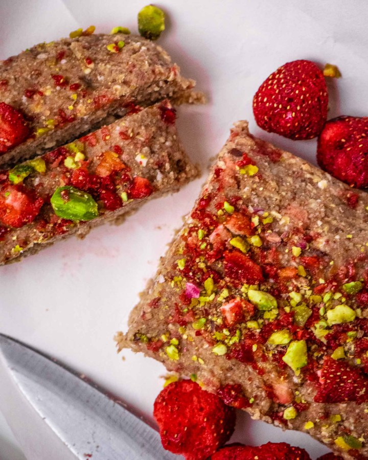 sliced raw protein strawberry cookie dough topped with freeze-dried strawberries and pistachios