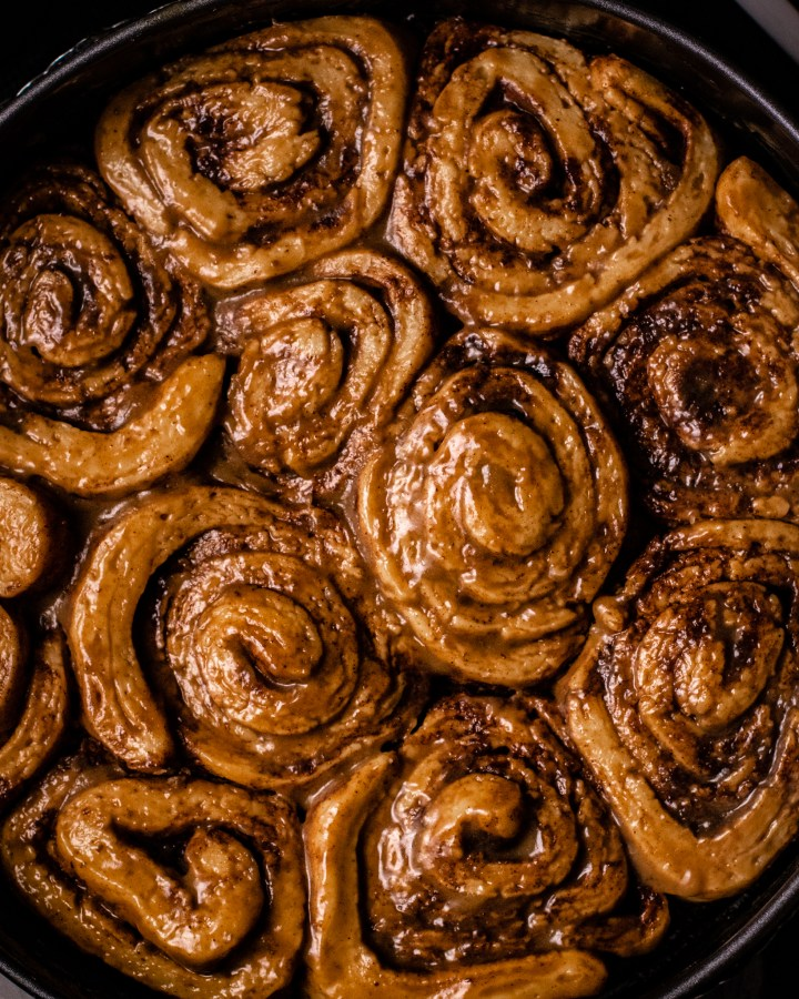 glossy cinnamon buns freshly baked in round tin