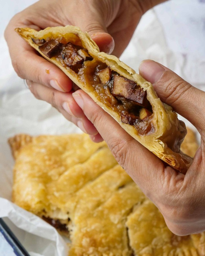 hand holding vegan steak bake cut in half with inside of puff pastry case filled with gravy and tofu steak