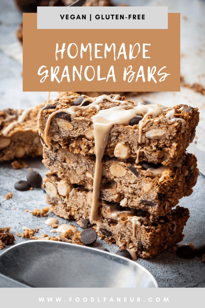 stack of oat, nut and chocolate chip granola bars drizzled with tahini on a rustic grey stone surface surrounded by oat crumbs and more bars