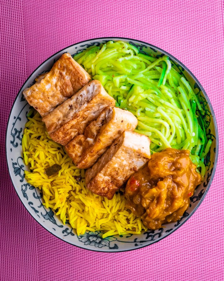 large bowl filled with yellow indian rice, mango chutney, cucumber raita and big rectangular fried tofu chunks  all composed in neat layers