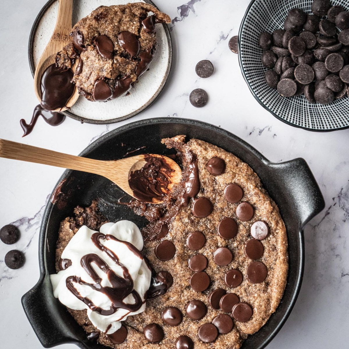 chocolate chip skillet cookie topped with scopp of vanilla ice cream on white marble table next to scattered chocolate chips