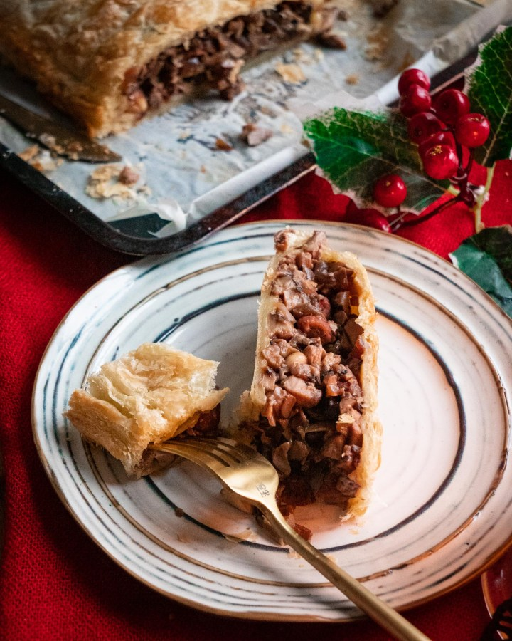 slice of vegan wellington with puff pastry morsel next to slice filled with meaty mushrooms and gravy on table decorated with holly