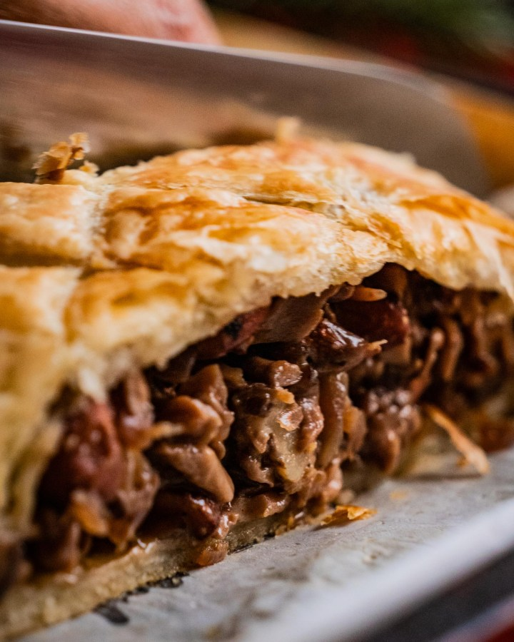 vegan wellington filled with creamy brown gravy, mushrooms and covered in flaky puff pastry