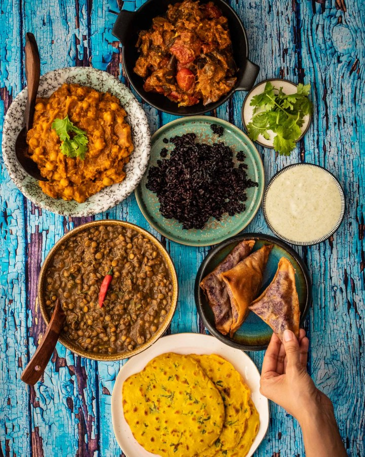 flatlay blue rustic wooden table laden with samosas, curries, pakoras, raita, chapattis and rice